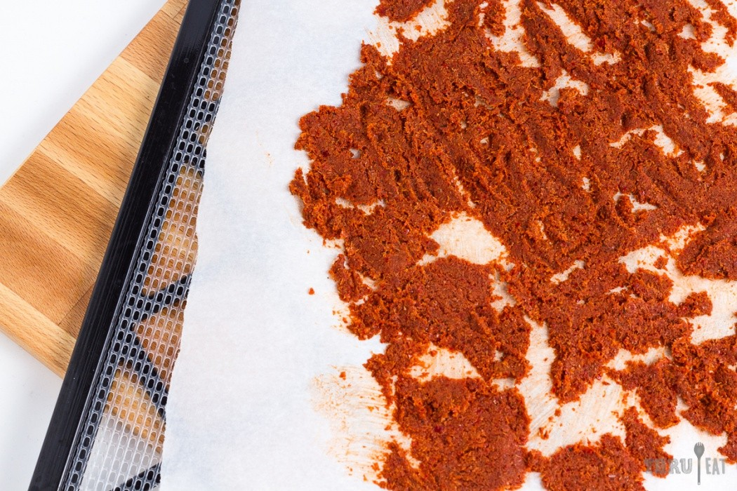 red curry paste spread on a dehydrator tray