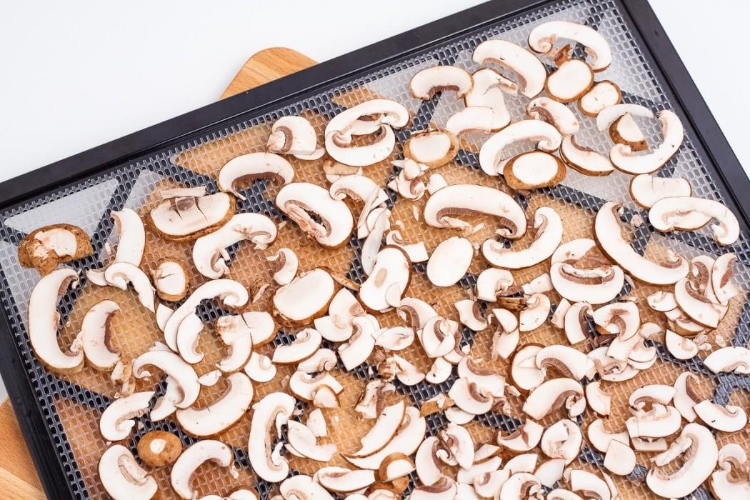 sliced baby bella mushrooms on a dehydrator tray