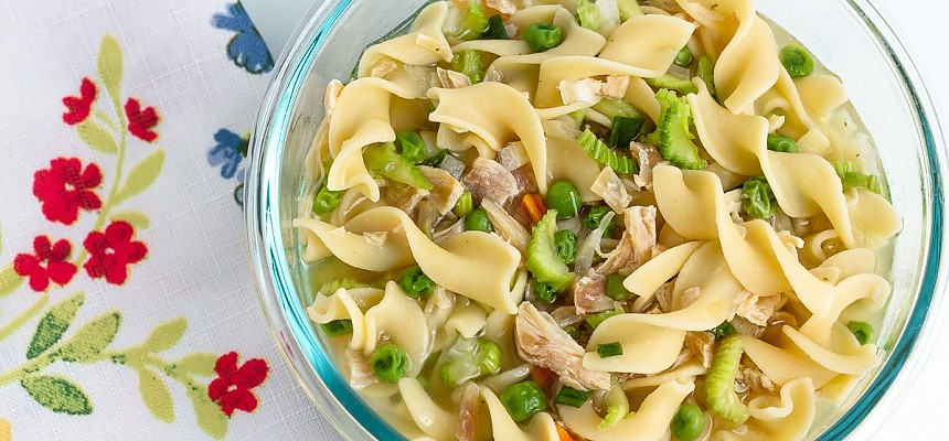 bowl of chicken noodle soup with peas, carrots, celery, and mushrooms