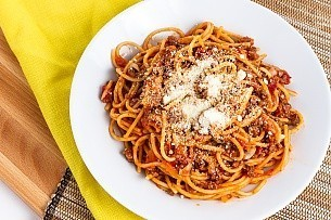 a bowl of spaghetti with parmesan cheese sprinkled on top
