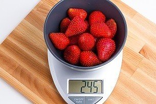 245 grams of strawberries in a blue bowl on a scale