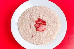 cooked strawberries and cream oatmeal on a red background