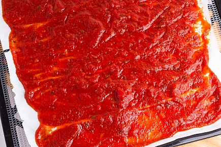 pasta sauce spread on parchment paper before dehydrating