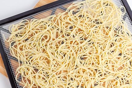 spaghetti noodles spread on a dehydrator tray