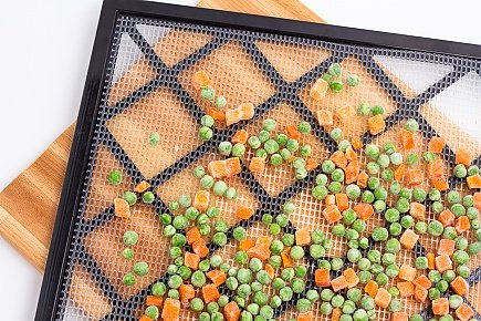 frozen peas and carrots on a dehydrator tray