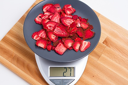 27 grams of dried strawberries on a blue plate on a scale