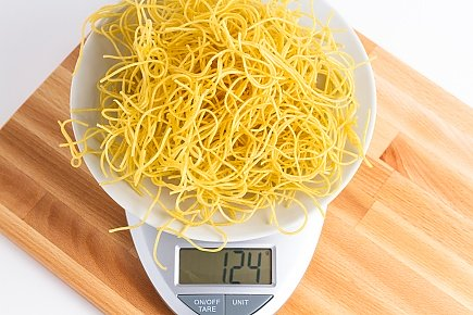 124 grams of dehydrated spaghetti noodles on a scale
